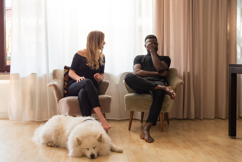 man and woman arguing with dog lying between them. Breakups are hard on pets